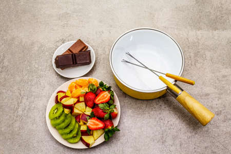 Chocolate fondue. Assorted fresh fruits, two types of chocolate. Ingredients for cooking a sweet romantic dessert. Stone concrete background