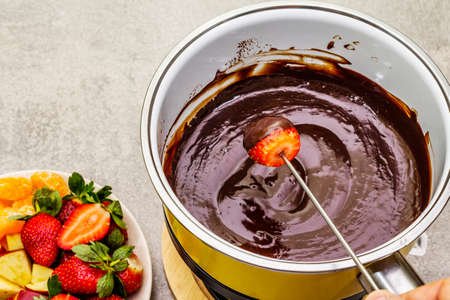 Chocolate fondue. Assorted fresh fruits, two types of chocolate, male hand. Ingredients for cooking a sweet romantic dessert. Stone concrete background 写真素材