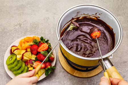 Chocolate fondue. Assorted fresh fruits, two types of chocolate, male and female hand. Ingredients for cooking a sweet romantic dessert. Stone concrete background