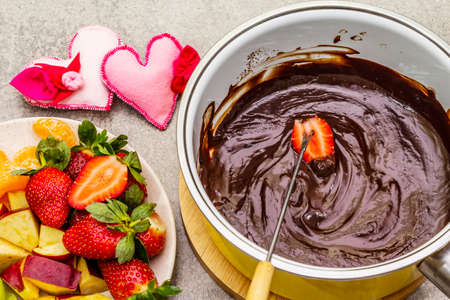 Chocolate fondue. Assorted fresh fruits, two types of chocolate, felt hearts. Ingredients for cooking a sweet romantic dessert. Stone concrete background Reklamní fotografie - 137799773