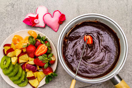 Chocolate fondue. Assorted fresh fruits, two types of chocolate, felt hearts. Ingredients for cooking a sweet romantic dessert. Stone concrete background