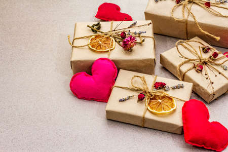 Zero waste gift concept. Valentine Day or Birthday eco friendly packaging. Festive boxes in craft paper with different organic decorations. Stone concrete background, copy space