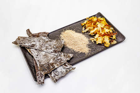 Set of traditional Japanese ingredient for cooking basic dashi broth. Algae kombu, katsuobushi and finished dry granules. Isolated on white background, copy space