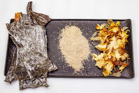 Set of traditional Japanese ingredient for cooking basic dashi broth. Algae kombu, katsuobushi and finished dry granules. Isolated on white background, top view, close up