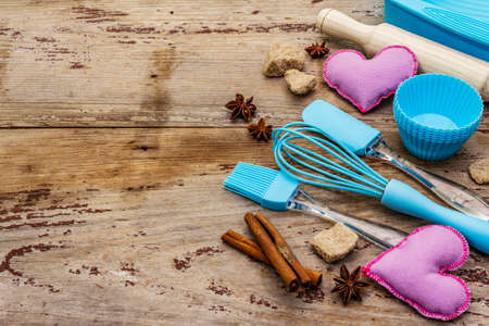 Valentines Day baking background. Silicone molds for cupcakes, spices, sugar, whisk, spatula, rolling pin and felt hearts. Old wooden boards, copy space