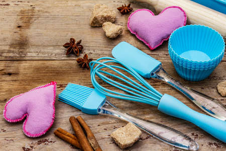 Valentines Day baking background. Silicone molds for cupcakes, spices, sugar, whisk, spatula, rolling pin and felt hearts. Old wooden boards, copy space, close up