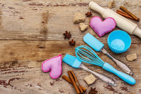 Valentines Day baking background. Silicone molds for cupcakes, spices, sugar, whisk, spatula, rolling pin and felt hearts. Old wooden boards, copy space, top view Reklamní fotografie - 138063717