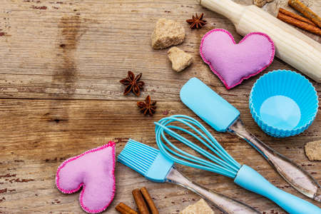 Valentines Day baking background. Silicone molds for cupcakes, spices, sugar, whisk, spatula, rolling pin and felt hearts. Old wooden boards, copy space, top view, close up