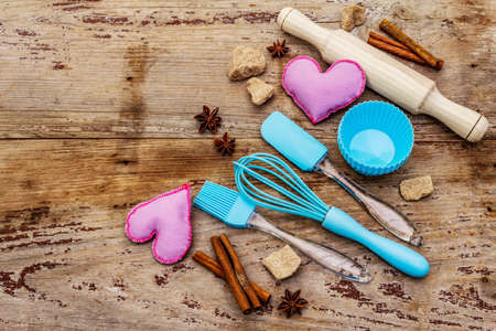 Valentines Day baking background. Silicone molds for cupcakes, spices, sugar, whisk, spatula, rolling pin and felt hearts. Old wooden boards, copy space, top view Reklamní fotografie - 138063716