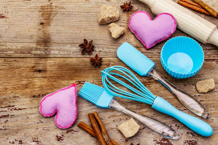 Valentines Day baking background. Silicone molds for cupcakes, spices, sugar, whisk, spatula, rolling pin and felt hearts. Old wooden boards, copy space, top view, close up Reklamní fotografie - 138063719