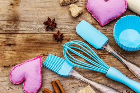 Valentines Day baking background. Silicone molds for cupcakes, spices, sugar, whisk, spatula, rolling pin and felt hearts. Old wooden boards, copy space, top view, close up Reklamní fotografie - 138063723