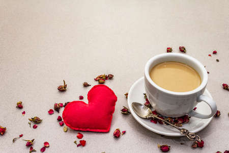 Good morning. Cup of coffee, rose buds and petals, red felt heart. Romantic breakfast, Valentines Day. Stone concrete background, copy space