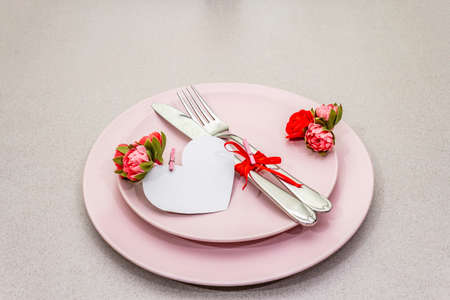 Romantic table setting on light stone concrete background. Valentine's day or Wedding card template. Paper heart, flowers, cutlery, copy space
