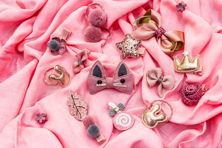 Little girl accessories lifestyle set. Gray-pink color scheme. Rose fabric background, top view, flat lay, close up 版權商用圖片