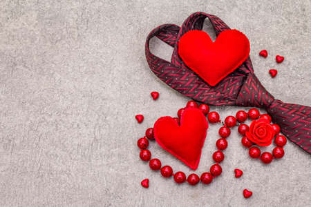 Valentines Day concept. Red felt hearts, women beads, men tie. Stone concrete background, top view, copy space