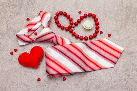 Valentines Day concept. Red felt hearts, women beads, men tie. Stone concrete background, top view, close up