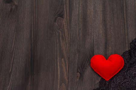 Liebeskonzept zum Valentinstag. Karte mit Platz für Text. Rotes Filzherz, Spitze, schwarzer Holzbretthintergrund, Kopienraum, Draufsicht Standard-Bild