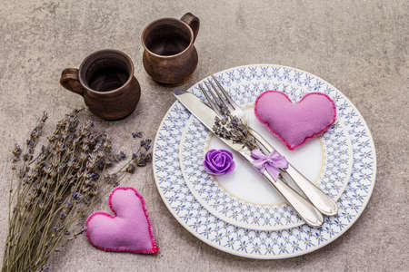 Romantic table setting on light stone concrete background. Valentine's day or Wedding card template. Lilac felt heart, lavender, rose flower, cutlery, cups, top view Standard-Bild