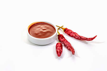 Spicy chili sauce in bowl isolated on white background. Different varieties of dry hot peppers, main ingredient for preparation. Cooking backdrop, mockup, copy space Stok Fotoğraf