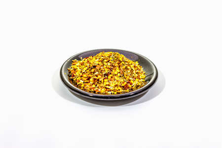 Hot seasoning in plate isolated on white background. Mix of different spices and sea salt. Traditional ingredient for cooking Italian food, copy space