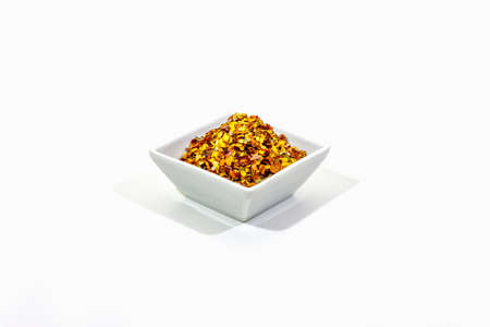 Hot seasoning in bowl isolated on white background. Mix of different spices and sea salt. Traditional ingredient for cooking Italian food, copy space