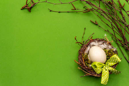 Easter zero waste decor, DIY concept. Design element and decor. Bird nest, egg, moss, birch branches, feather. Green background, top view, copy space