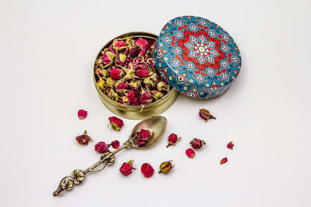 Traditional Turkish rose bud tea isolated on white background. Tin box, characteristic pattern, silver spoon, dry flowers, petals. Healthy lifestyle concept Foto de archivo