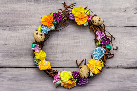 Hand crafted Easter wicker wreath with quail eggs and handmade flowers. Birch branches, polka dot satin ribbon. Stay at home concept. Festive Easter gray wooden background, top view 版權商用圖片