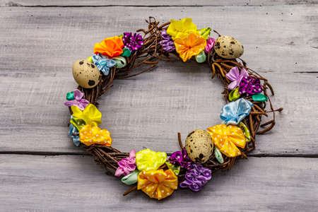 Hand crafted Easter wicker wreath with quail eggs and handmade flowers. Birch branches, polka dot satin ribbon. Stay at home concept. Festive Easter gray wooden background