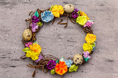Hand crafted Easter wicker wreath with quail eggs and handmade flowers. Birch branches, polka dot satin ribbon. Stay at home concept. Festive Easter gray background, top view