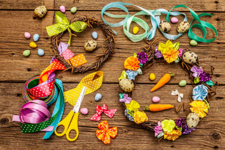 Hand crafted Easter wicker wreath with quail eggs and handmade flowers. Set of materials and tools for needlework. Stay at home concept. Festive Easter old wooden background, top view