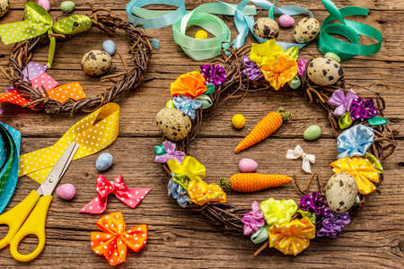 Hand crafted Easter wicker wreath with quail eggs and handmade flowers. Set of materials and tools for needlework. Stay at home concept. Festive Easter old wooden background 版權商用圖片