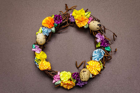 Hand crafted Easter wicker wreath with quail eggs and handmade flowers. Birch branches, polka dot satin ribbon. Stay at home concept. Festive Easter black background, top view