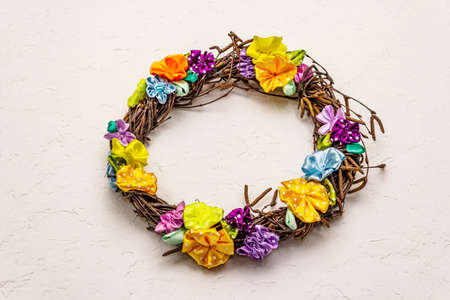 Spring composition of a wreath of birch branches and craft colorful flowers. Handmade from satin polka dot ribbons, stay at home concept. White putty background 版權商用圖片
