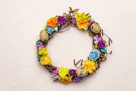 Hand crafted Easter wicker wreath with quail eggs and handmade flowers. Birch branches, polka dot satin ribbon. Stay at home concept. Festive Easter white putty background, top view 版權商用圖片