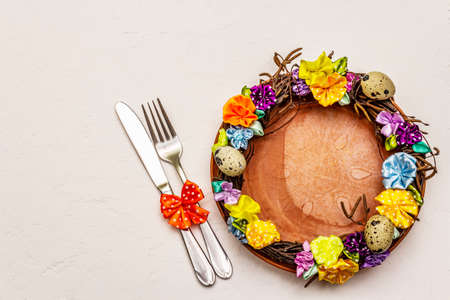 Festive Easter table setting. Hand crafted Easter wicker wreath with quail eggs and handmade flowers. Birch branches, polka dot satin ribbon. White putty background, top view