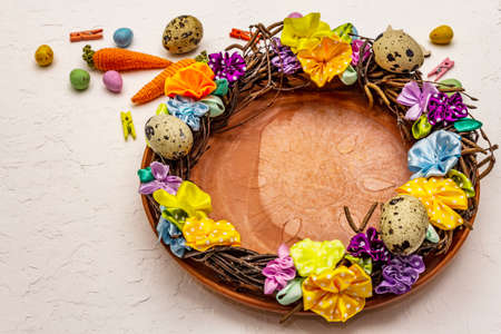 Festive Easter table setting. Hand crafted Easter wicker wreath with quail eggs and handmade flowers. Birch branches, polka dot satin ribbon. White putty background, close up