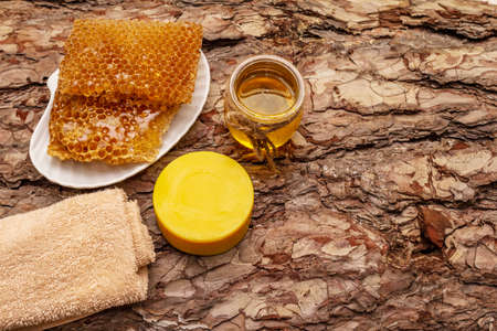 Spa concept. Self care with honey and honeycombs. Natural organic cosmetics, homemade product, alternative lifestyle. Wooden bark background Standard-Bild