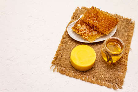 Spa concept. Self care with honey and honeycombs. Natural organic cosmetics, homemade product, alternative lifestyle. White putty background