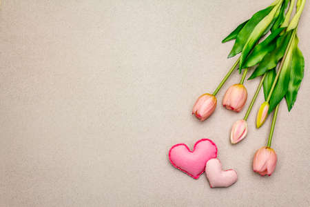 Greetings card, wallpaper, backdrop. Happy Mothers Day, St.Valentines or Wedding. Gentle pink tulips, handmade felt hearts. Stone concrete background