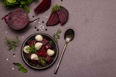 Culinary background. Cooking food concept. Healthy salad with baked beetroot, baby mozzarella, fresh greens. Trendy black stone concrete backdrop, top view Imagens
