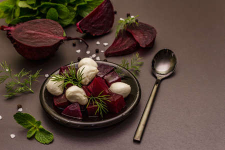 Culinary background. Cooking food concept. Healthy salad with baked beetroot, baby mozzarella, fresh greens. Trendy black stone concrete backdrop, close up