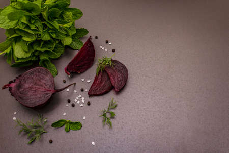 Culinary background. Cooking food concept. Beetroot, fresh mint, dill, sea salt, peppercorn. Trendy black stone concrete backdrop, copy space