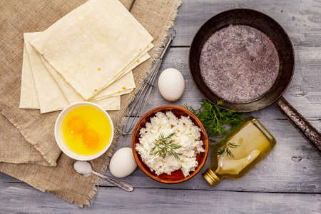 Set of products for cooking hot snack. Pita bread, cottage cheese, eggs, greens, vegetable oil. Vintage frying pan, wooden boards background