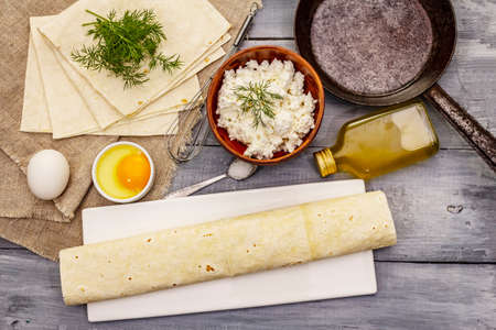 Set of products for cooking hot snack. Pita bread, cottage cheese, eggs, greens, vegetable oil. Vintage frying pan, wooden boards background Imagens