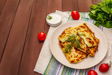 Hot appetizer - pita bread with cheese and herbs. Vegetarian healthy food. Wood table background, copy space