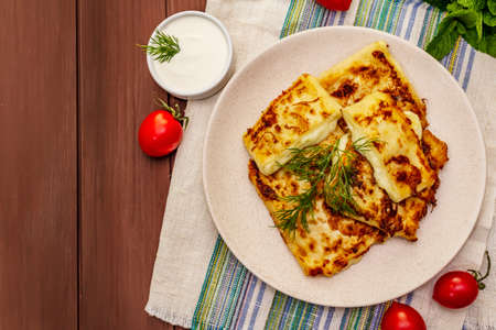 Hot appetizer - pita bread with cheese and herbs. Vegetarian healthy food. Wood table background, top view Imagens