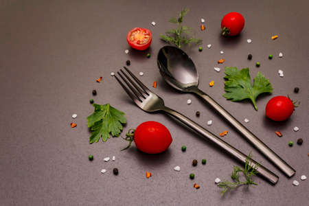 Culinary background. Cooking food concept. Cutlery, fresh vegetables, spices, herbs. Trendy black stone concrete backdrop, copy space