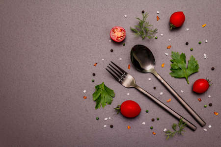 Culinary background. Cooking food concept. Cutlery, fresh vegetables, spices, herbs. Trendy black stone concrete backdrop, copy space, top view