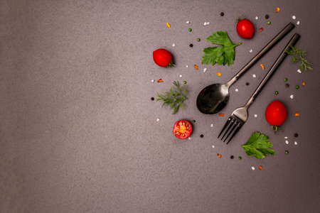Culinary background. Cooking food concept. Cutlery, fresh vegetables, spices, herbs. Trendy black stone concrete backdrop, copy space, top view Imagens